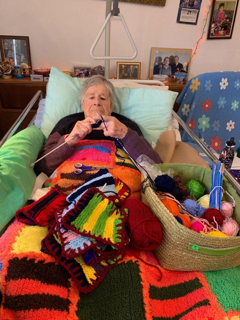 """Una anziana signora lavora a maglia per contribuire al progetto """"coperte per senza dimora""""."""